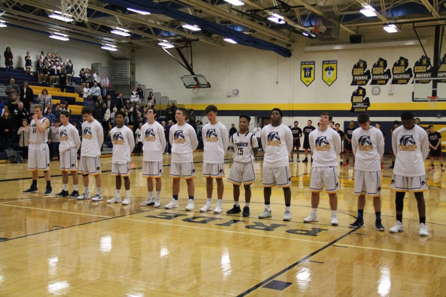 The+boys+basketball+team+stand+side+by+side+in+silence+during+the+national+anthem+before+playing+the+Reds+of+Port+Huron+on+January+16th%2C+2018