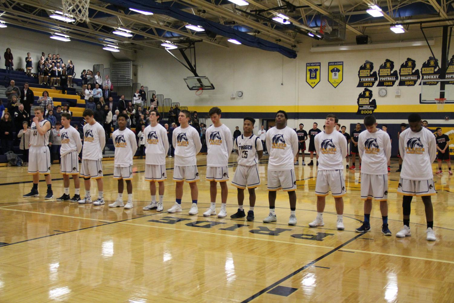 The boys basketball team stand side by side in silence during the national anthem before playing the Reds of Port Huron on January 16th, 2018