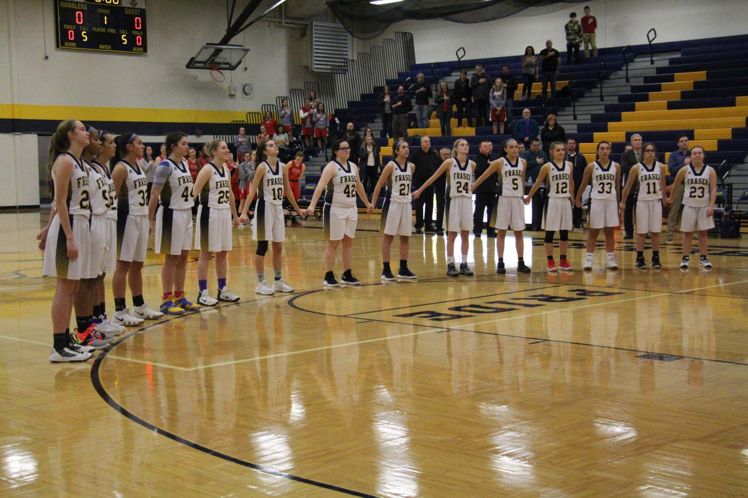 The Lady Ramblers stand together as the National Anthem plays over the gym.