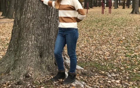 Ashlyn Baker is leaning against a tree at Licht Park. She loves going to the park and exploring nature.