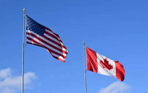 A Canadian and an American flag waving through the cold spring wind. At the Border between the two neighboring nations.