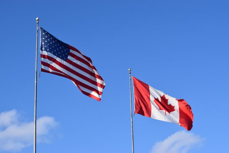 A+Canadian+and+an+American+flag+waving+through+the+cold+spring+wind.+At+the+Border+between+the+two+neighboring+nations.+